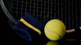 Chiuda su del tennis della racchetta della pallina da tennis e della cinghia di polso nel nero con la riflessione qui sotto immagini stock libere da diritti