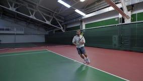 Chiuda su del tennis professionista bello in camicia bianca, shorts grigi e scarpe preparantesi alla corte dell'interno con video d archivio