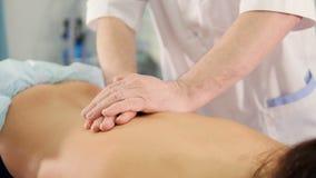 Chiuda su del terapista di massaggio che massaggia la parte posteriore del ` s della donna stock footage