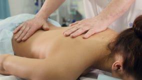 Chiuda su del terapista di massaggio che massaggia la parte posteriore del ` s della donna archivi video
