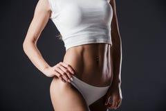 Chiuda su del torso della donna di misura con le sue mani sulle anche La femmina con l'addome perfetto muscles su fondo nero Immagini Stock Libere da Diritti