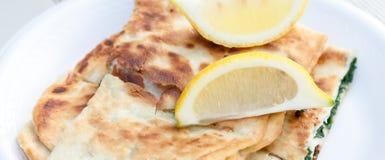 Chiuda su del turco Gozleme del formaggio degli spinaci con i cunei di limone Fotografia Stock Libera da Diritti