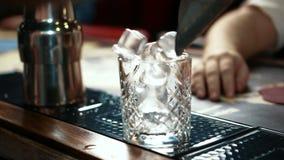 Chiuda su del vetro del whiskey che è compiuto con il ghiaccio nella barra alla moda, movimento lento stock footage