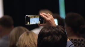 Chiuda su del video della registrazione con lo smartphone all'evento azione Video umano del tiro delle mani sul telefono stock footage