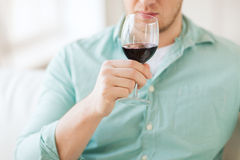 Chiuda su del vino bevente dell'uomo a casa Fotografia Stock