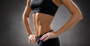 Chiuda su dell'ABS femminile atletico in abiti sportivi Fotografia Stock