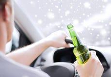 Chiuda su dell'alcool bevente dell'uomo mentre conducono l'automobile Immagine Stock