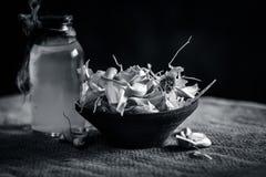 Chiuda su dell'allium sativum, aglio con il suo olio in una bottiglia trasparente Fotografie Stock Libere da Diritti