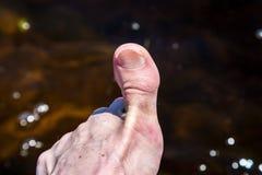 Chiuda su dell'alluce contro l'acqua luccicante Immagine Stock