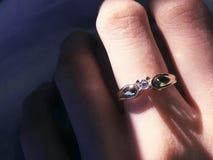 Chiuda su dell'anello di diamante elegante sul dito con il fondo grigio della sciarpa Diamond Ring immagini stock