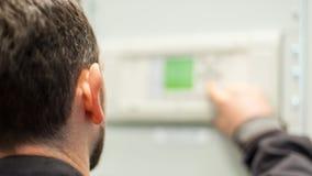 Chiuda su dell'apparecchiatura elettrica di comando di tensione di prova dell'ingegnere di manutenzione immagine stock