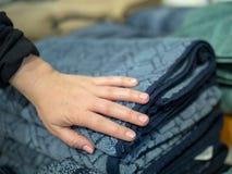 Chiuda su dell'asciugamano blu commovente della mano dei woman's fotografia stock libera da diritti