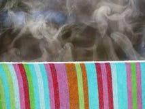 Chiuda su dell'asciugamano variopinto bagnato che appende fuori in inverno e vapori a causa dei raggi di sole caldi immagine stock