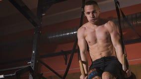 Chiuda su dell'atleta senza camicia che fa l'esercizio del muscolo-su sugli anelli di sport archivi video