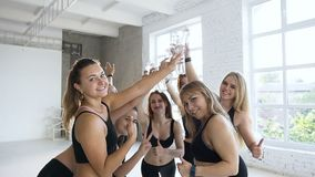 Chiuda su dell'giovani donne felici battono le bottiglie di acqua dopo la formazione nella palestra Sport e stile di vita sano video d archivio