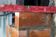 Chiuda su dell'industriale di lavoro di muratura che installa i mattoni sul construc fotografia stock libera da diritti