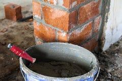 Chiuda su dell'industriale di lavoro di muratura che installa i mattoni sul construc fotografie stock