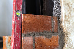 Chiuda su dell'industriale di lavoro di muratura che installa i mattoni sul construc immagini stock