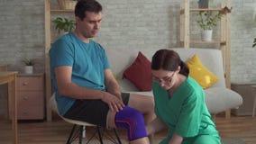 Chiuda su dell'infermiere contribuisce a tirare la fasciatura sul ginocchio di un atleta dell'uomo archivi video