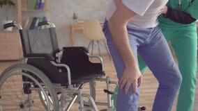 Chiuda su dell'infermiere musulmano nel hijab aiuta il disabile a alzarsi dalla sedia a rotelle archivi video
