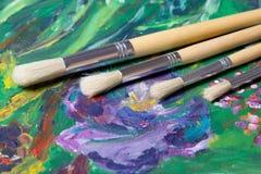 Chiuda su dell'insieme dei pennelli e della pittura acrilica Fotografia Stock
