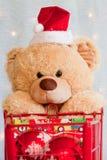 Chiuda in su dell'orso di orsacchiotto di natale e del carrello di acquisto Immagini Stock