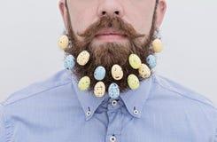 Chiuda su dell'uomo barbuto bello con le uova di Pasqua fotografia stock
