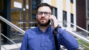 Chiuda su dell'uomo barbuto bello vestito in camicia blu che sta all'aperto e che parla sul telefono Il giovane uomo d'affari è archivi video