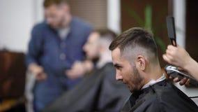 Chiuda su dell'uomo barbuto che si siede con il capo nero di taglio in parrucchiere Il barbiere femminile sta facendo la forma pe video d archivio