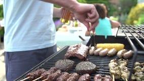 Chiuda su dell'uomo che cucina sul barbecue a casa stock footage