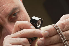 Chiuda su dell'uomo che esamina i gioielli tramite la lente d'ingrandimento Fotografia Stock