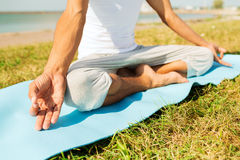 Chiuda su dell'uomo che fa gli esercizi di yoga all'aperto fotografia stock