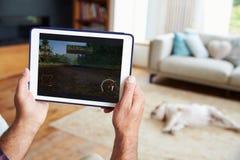 Chiuda su dell'uomo che gioca il gioco sulla compressa di Digital a casa Fotografie Stock