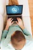 Chiuda su dell'uomo che lavora con il computer portatile a casa Immagini Stock