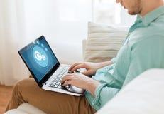Chiuda su dell'uomo che lavora con il computer portatile a casa Fotografia Stock