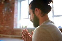 Chiuda su dell'uomo che medita allo studio di yoga Immagine Stock