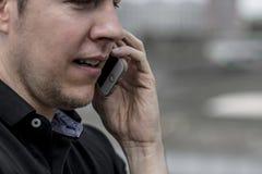 Chiuda su dell'uomo che parla su un telefono cellulare immagini stock