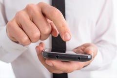 Chiuda su dell'uomo che per mezzo del touch screen Smartphone Fotografie Stock Libere da Diritti