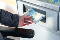 Chiuda su dell'uomo che prende i contanti, euro dal BANCOMAT immagine stock libera da diritti
