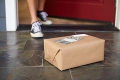 Chiuda su dell'uomo che raccoglie la consegna del pacchetto fuori della porta Immagine Stock