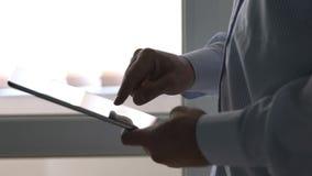Chiuda su dell'uomo che scrive sul computer della compressa con il suo dito stock footage