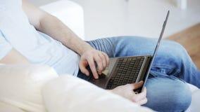 Chiuda su dell'uomo che scrive sul computer portatile a casa video d archivio