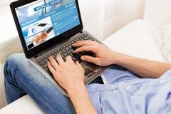 Chiuda su dell'uomo che scrive sul computer portatile a casa Immagine Stock