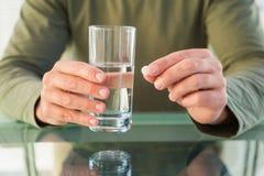 Chiuda su dell'uomo che tiene una pillola e un bicchiere d'acqua Immagine Stock