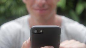 Chiuda su dell'uomo che usando Smartphone all'aperto Giovane con il computer della compressa Un uomo al giardino sulle reti socia stock footage