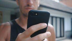 Chiuda su dell'uomo che usando Smartphone all'aperto Giovane con il computer della compressa Un uomo all'iarda vicino alla casa s video d archivio