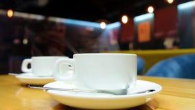 Chiuda su dell'uomo che versa il tè caldo nelle tazze bianche Tè dell'agrume della vitamina in caffè stock footage