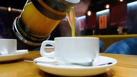Chiuda su dell'uomo che versa il tè caldo nelle tazze bianche Tè dell'agrume della vitamina in caffè video d archivio