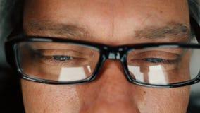 Chiuda su dell'uomo con gli occhi azzurri che legge e che decolla gli occhiali per sfregare i suoi occhi stock footage