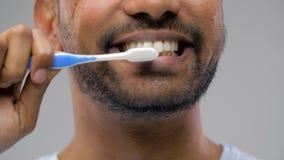 Chiuda su dell'uomo con i denti di pulizia dello spazzolino da denti stock footage